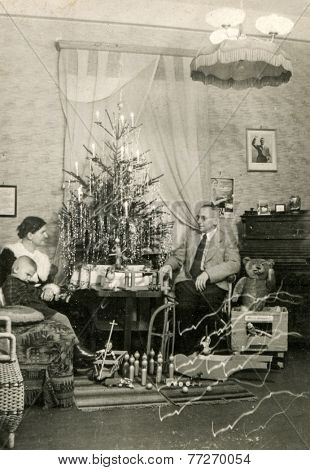 GERMANY, CIRCA DECEMBER 1924:  Vintage photo of family sitting near Christmas tree while Adolf Hitler portrait hangs on wall