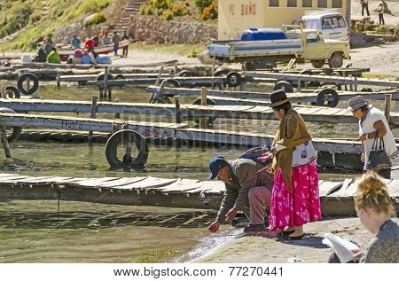 COPACABANA, BOLIVIA, MAY 7, 2014:  Local woman in traditional attire with her husband wash hands in water on jetty in port (Titicaca lake)