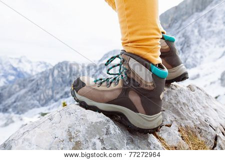 Close up of womans legs in heavy hiking boots standing on top of mountain