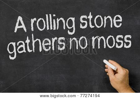 A rolling stone gathers no moss written on a blackboard
