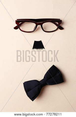 Glasses, mustache and bow tie forming man face on beige background