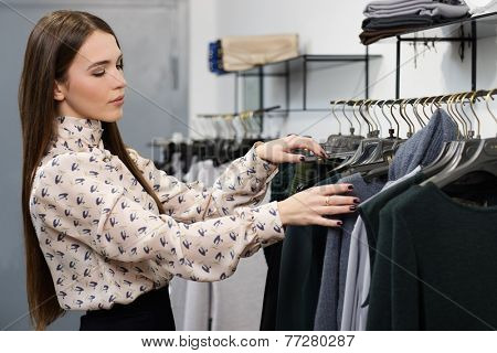 Young woman choosing clothes on a rack in a showroom