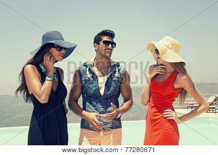 group of friends chatting and having fun at the pool, three stylish friends standing by the pool / s