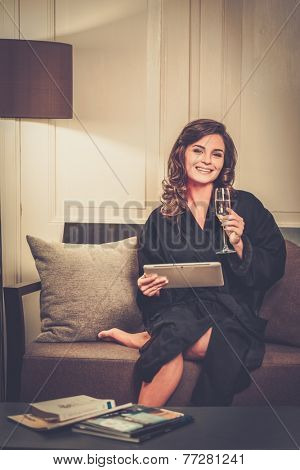Woman in bathrobe relaxing with glass of champagne and  tablet pc