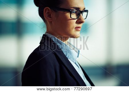 Pensive businesswoman in eyeglasses and formalwear