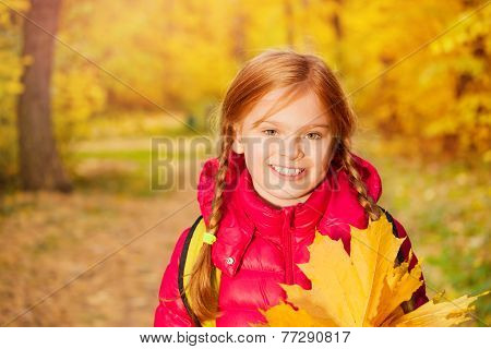 Close-up view of girl with rucksack and maple leaf