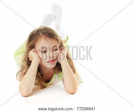 Thoughtful little girl lies on a white background.