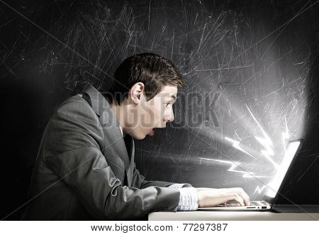 Young man looking in laptop screen with shock