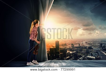 Young woman in casual with violin opening curtain
