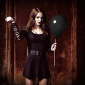 image of piercings  - A weird angry girl is piercing a black balloon by needle - JPG
