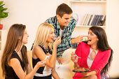 picture of couch  - Three pretty girls sitting on the couch eating cake a guy who stands behind them leaning against the couch rubbing nose girl with a filling of cake - JPG