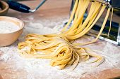 foto of pasta  - fresh pasta and pasta machine on kitchen table - JPG