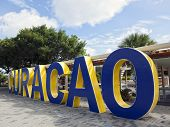 stock photo of curacao  - Word Curacao written in blue and yellow painted concrete letters at Queen Wilhelmina Park - JPG