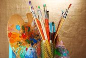 foto of paint palette  - Paint brushes with paints and palette on beige background - JPG