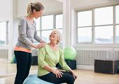 picture of personal care  - Female instructor assisting senior woman exercising in health club - JPG