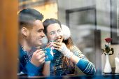 picture of iroquois  - Young loving couple dressed in blue sweater sitting with knitted coffee cups at the cafe in winter - JPG