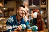 image of iroquois  - Young loving couple dressed in blue sweater sitting with knitted coffee cups in the cafe in winter - JPG