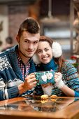 stock photo of iroquois  - Young loving couple dressed in blue sweater sitting with knitted coffee cups in the cafe in winter - JPG