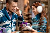 pic of iroquois  - Man making proposal giving a gift box to his girlfriend dressed in blue sweaters in the cafe - JPG