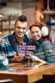 foto of iroquois  - Young couple dressed in blue knitted sweaters with gift boxes at the cafe in winter - JPG