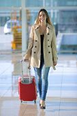 stock photo of carry-on luggage  - Front view of a traveler woman walking carrying a suitcase in an airport corridor - JPG
