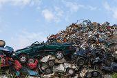 foto of junk-yard  - Scrap yard with crushed cars and blue sky - JPG