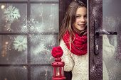 foto of cold-weather  - Child girl welcome guests and holding holiday lantern - JPG