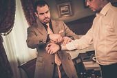 pic of tailoring  - Tailor measuring client for custom made suit tailoring - JPG