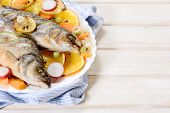 foto of bass fish  - Bass fish prepared in the plate on wooden background with blank space - JPG