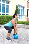 pic of kettlebell  - Beautiful sporty hispanic woman in blue training with kettlebell doing dead lift - JPG