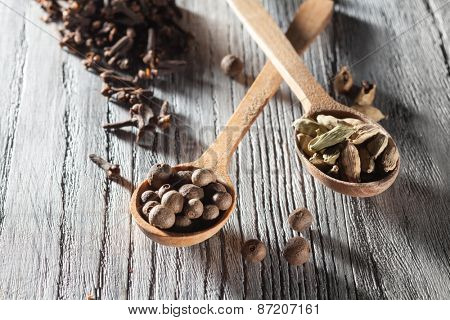 Nutmeg, clove and allspice in old spoon on wooden background