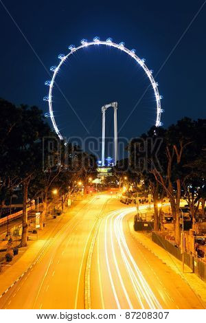 SINGAPORE - APR 5: Singapore Flyer at night with traffic on April 5, 2013 in Singapore. It is 4th largest financial center and 1 of 5 world busiest ports.