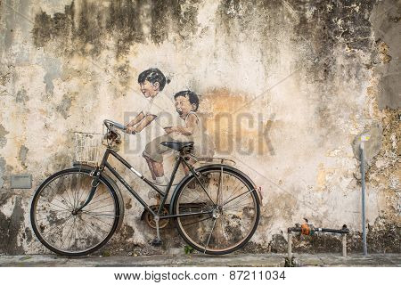 Georgetown, Penang, Malaysia - March 1, 2015: Famous graffiti of little children on a bicycle in Georgetown, Penang by Lithuanian artist Ernest Zacharevic