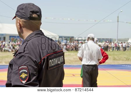 policeman in a baseball cap looks thoughtfully into the distance