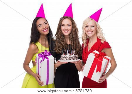 Happy three women with birthday hats and colourful presents