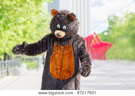 actor dressed as bear walks avenue of park on background of red stars