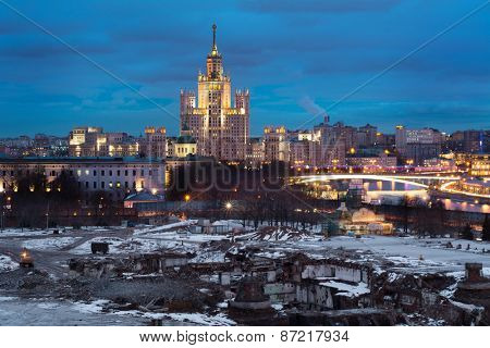 Apartment house on Kotelnicheskaya Embankment and place for construction on site hotel Russia in Moscow in evening