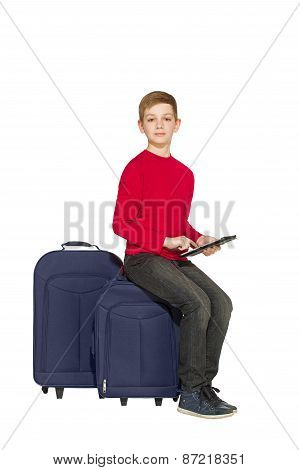 Boy Sitting On Travel Bags Holding Tablet Isolated On White