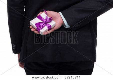 Close up of man hand holding present behind back