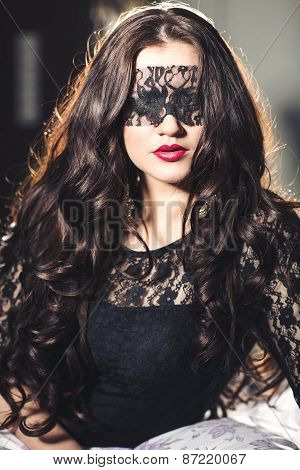 beautiful young brunette woman with red lips and blindfolded