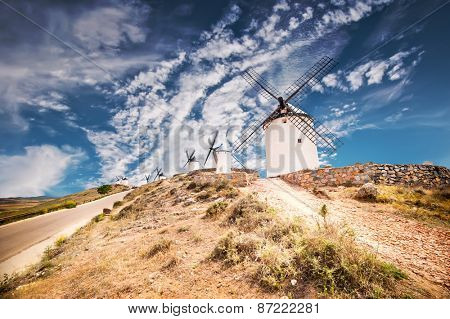 traditional windmills and castle in Consuegra against blue sky, Toledo, Spain
