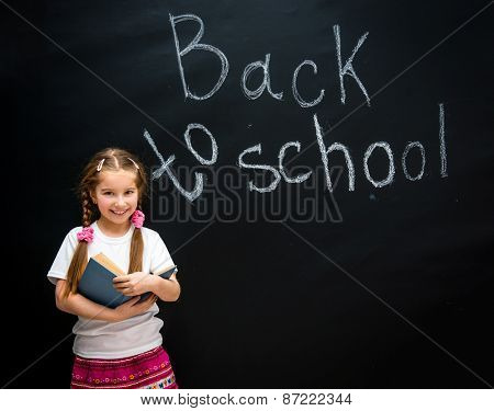 cute little girl with a blue book in hand smiling on black background blackboard with back to school
