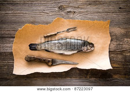 fresh trout with a knife and fork on a dark background