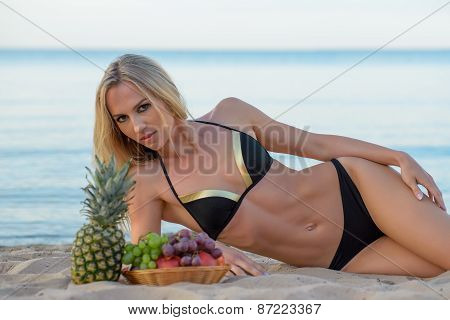 woman in  bikini relaxing on the sand with fruits