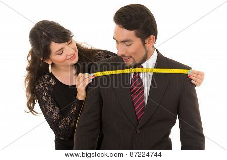 young woman tailor designer taking measures of client