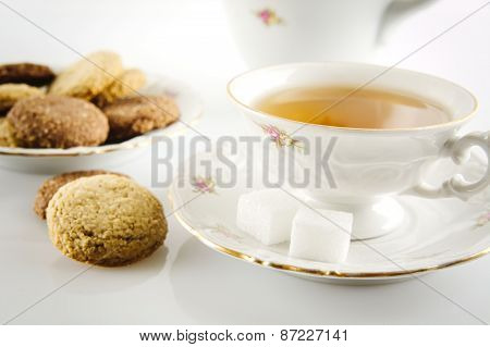Old-style Shot Kettle With Cup Of Tea With Cookies Foreground On