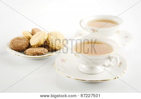 Old-style Shot Of Cup Of Tea With Cookies On White