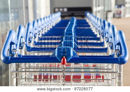 Row Of Paid Luggage Carts With A Coin Space And Chain Closeup At Modern Airport