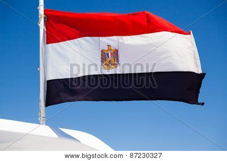 Waved egyptian flag on blue background