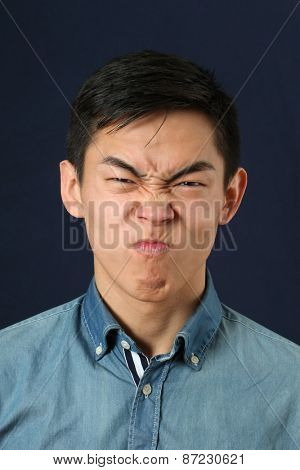 Disgusted young Asian man making face and looking at camera